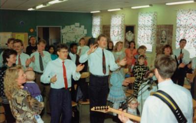 Lovsång och överlåtelse har karaktäriserat  församlingen hela tiden. Denna bild är från ett  möte i Enåkers Bygdegård i början av 1990-talet.  Längst till vänster ser vi Dave & Chris Richards.